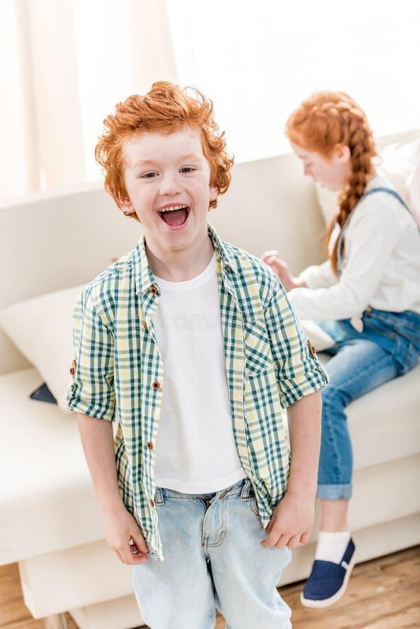 Porträt des entzückenden kleinen Jungen, der während kleine Schwester spielt auf Sofa lacht stockfotografie