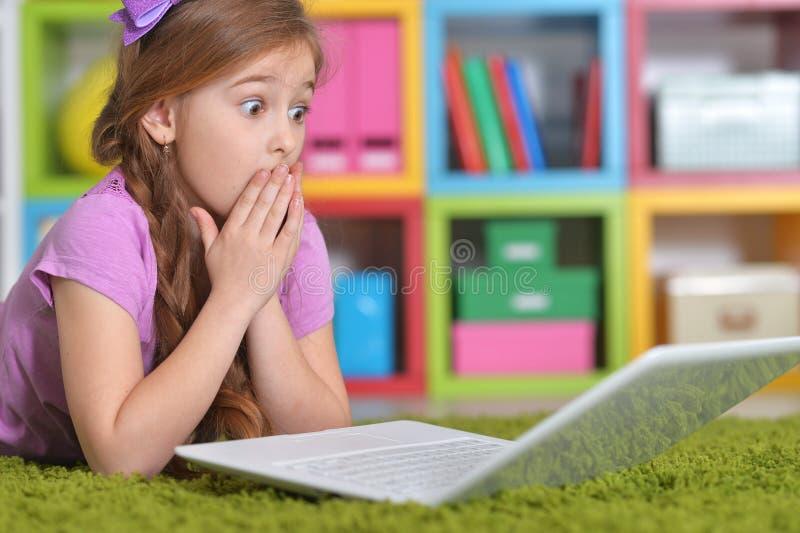 Porträt des entzückenden kleinen Mädchens unter Verwendung des modernen Laptops beim Lügen auf Boden stockfotos