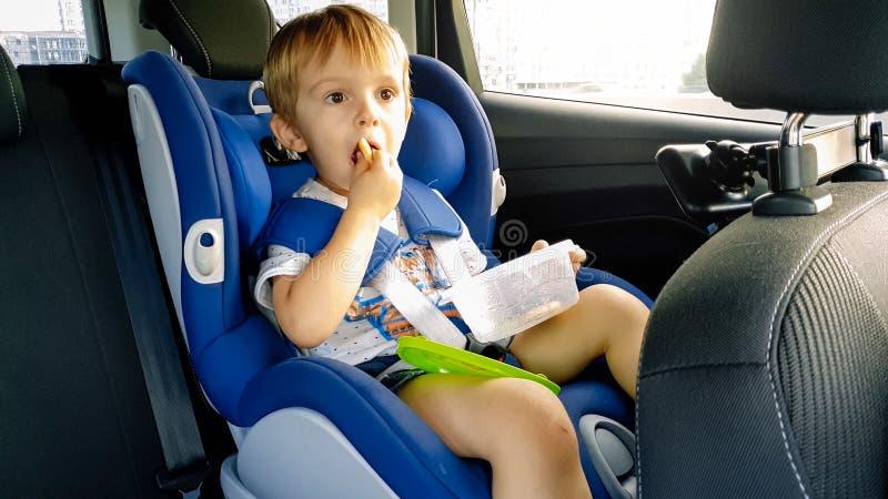 Porträt des entzückenden Kleinkindjungen, der im Kinderkindersitz sitzt und Plätzchen isst lizenzfreie stockfotos