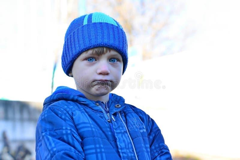 Porträt des entzückenden Kleinkindjungen mit dem langen blonden Haar, das draußen mit Schneebällen spielt Kind mit dem blauen Sch stockfotografie