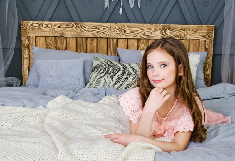 Porträt des entzückenden lächelnden Kindes des kleinen Mädchens in Prinzessinkleid, das auf dem Bett liegt lizenzfreie stockbilder