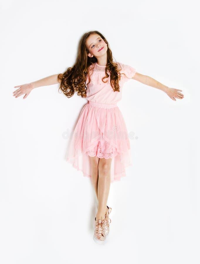 Porträt des entzückenden lächelnden Kindes des kleinen Mädchens in Prinzessinkleid mit dem Lockenhaar, das auf einem Boden lokali lizenzfreie stockfotografie