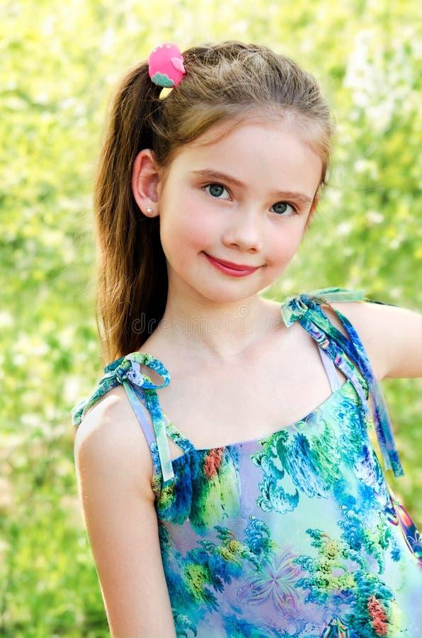 Porträt des entzückenden lächelnden kleinen Mädchens im Freien stockfoto