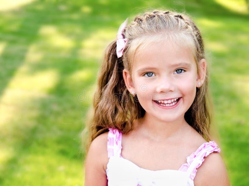 Porträt des entzückenden lächelnden kleinen Mädchens im Park lizenzfreies stockfoto