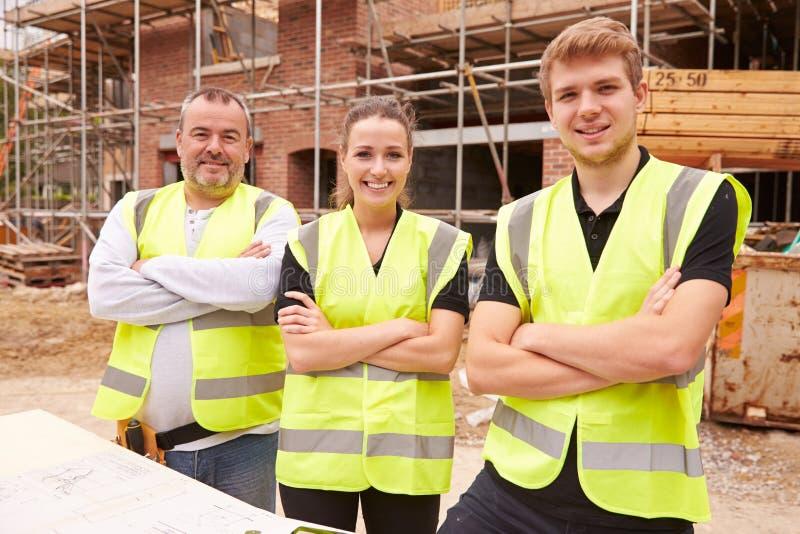 Porträt des Erbauers On Building Site mit Lehrlingen lizenzfreie stockfotos