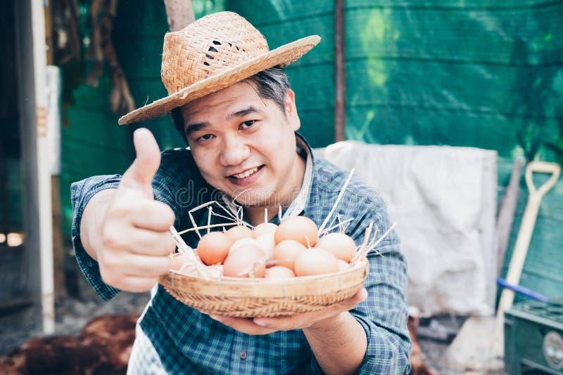 Porträt des erfüllten aufgeregten fleißigen herrlichen freuenden hübschen freundlichen netten Landwirts, der kleinen Korb hält stockfoto