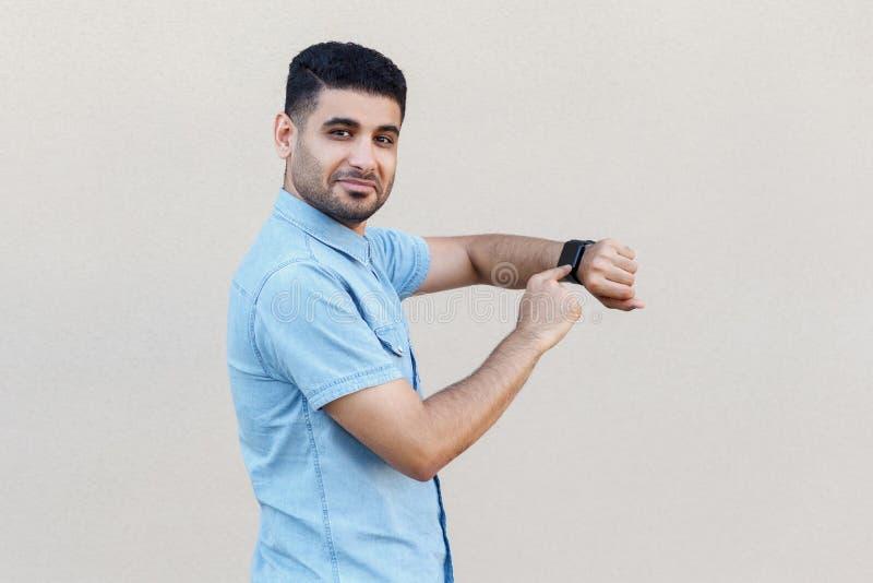 Portr?t des erf?llten h?bschen jungen b?rtigen Mannes im blauen Hemd, das seine intelligente Uhr, Kamera betrachtend steht, zeigt stockbild