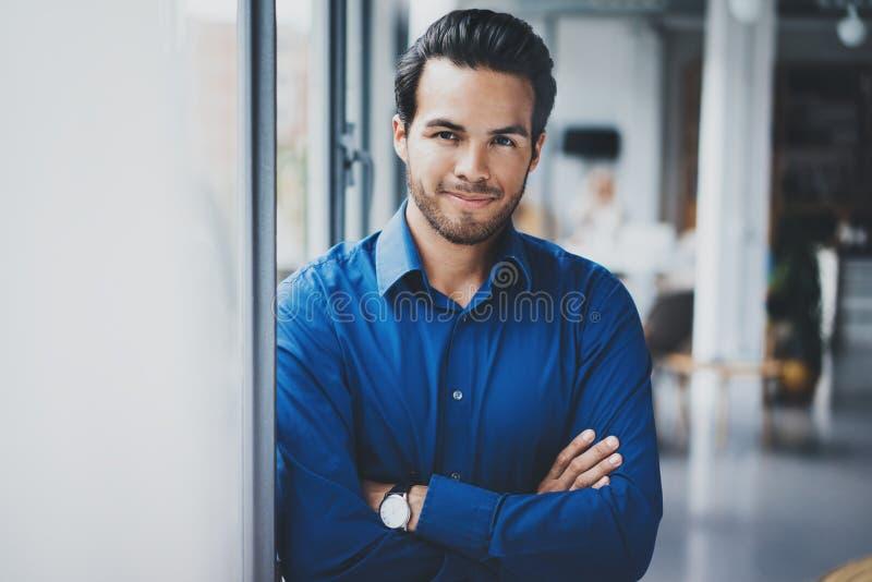 Porträt des erfolgreichen überzeugten hispanischen Geschäftsmannes, der nah vom Fenster im modernen Büro lächelt und steht lizenzfreie stockfotos