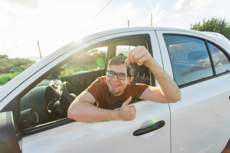 Porträt des erfolgreichen jungen glücklichen Mannes, der die Schlüssel sitzen im Neuwagen zeigt Selbstkauf- und Leutekonzept lizenzfreie stockfotografie