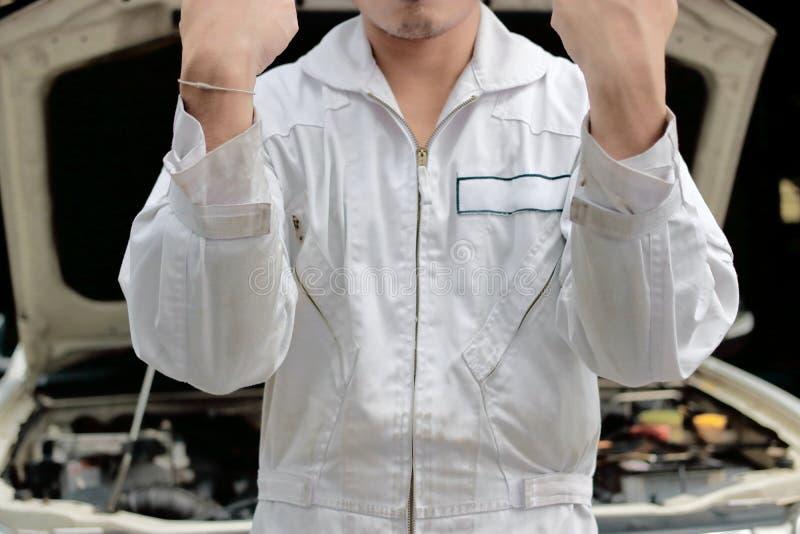 Porträt des erfolgreichen Mechanikermannes in der Uniform, die oben Hände mit Auto in der offenen Haube am Reparaturgaragenhinter stockfotos