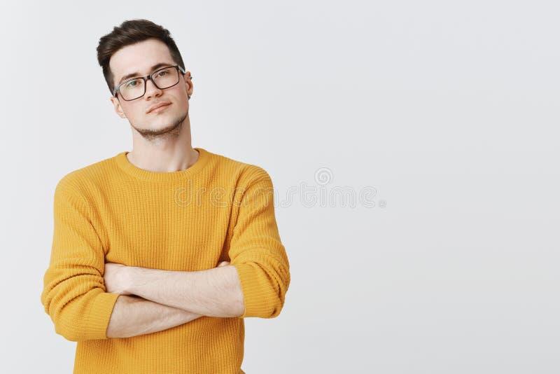Porträt des ernst-aussehenden hübschen und intelligenten jungen Mannes in den Gläsern und in gelber Strickjacke, die mit Ungläubi stockfoto