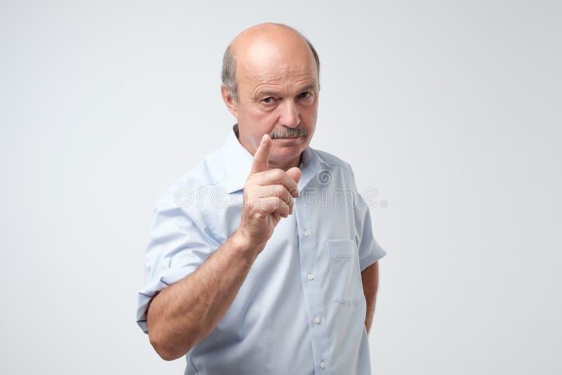 Porträt des ernsten älteren Mannes mit dem warnenden Finger und blauem Hemdhemd gegen hellgrauen Hintergrund lizenzfreie stockfotos