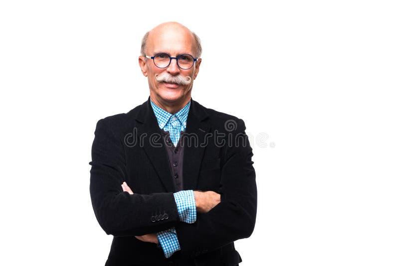Porträt des ernsten älteren Mannes wirft mit den gekreuzten Händen auf, die auf weißem Hintergrund lokalisiert werden lizenzfreies stockbild