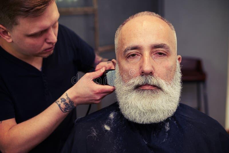 Porträt des ernsten attraktiven älteren Mannes im Friseursalon stockbild