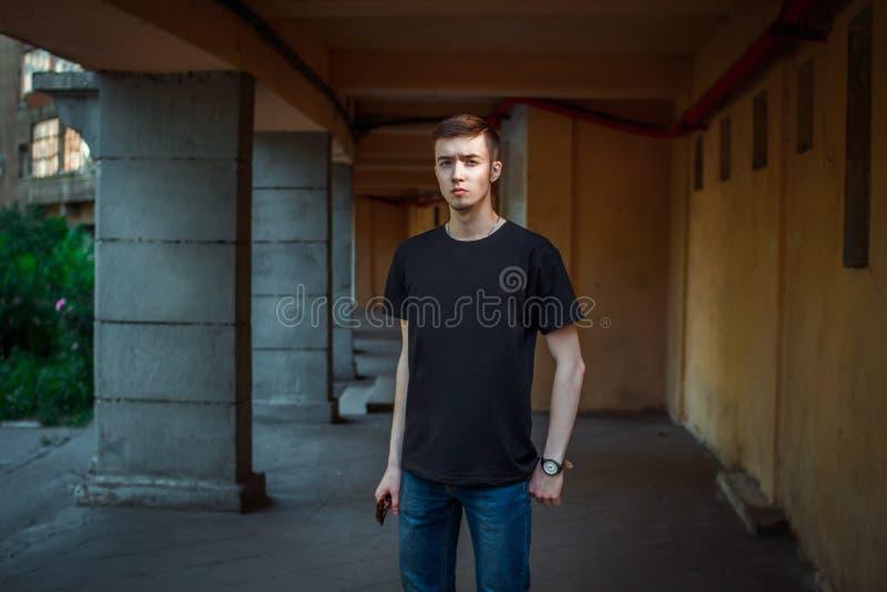 Porträt des ernsten hübschen jungen Mannes, der nahen Altbau steht lizenzfreie stockfotografie