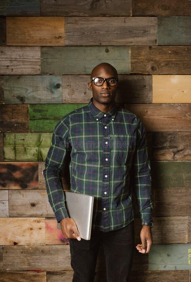 Porträt des ernsten jungen afrikanischen Mannes mit einem Laptop lizenzfreie stockfotos