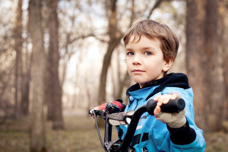 Porträt des ernsten Jungen mit Fahrrad im Park lizenzfreies stockbild