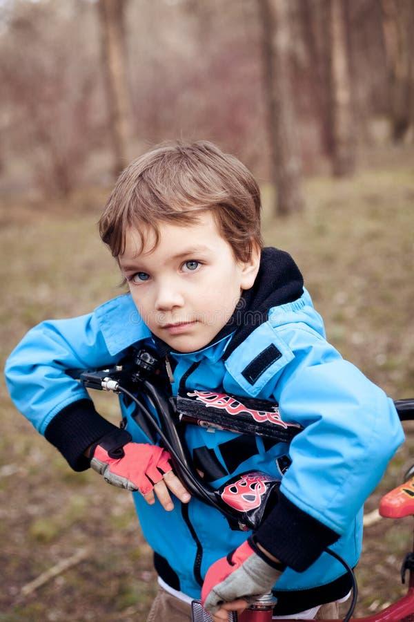 Porträt des ernsten Jungen mit Fahrrad im Park lizenzfreie stockfotos