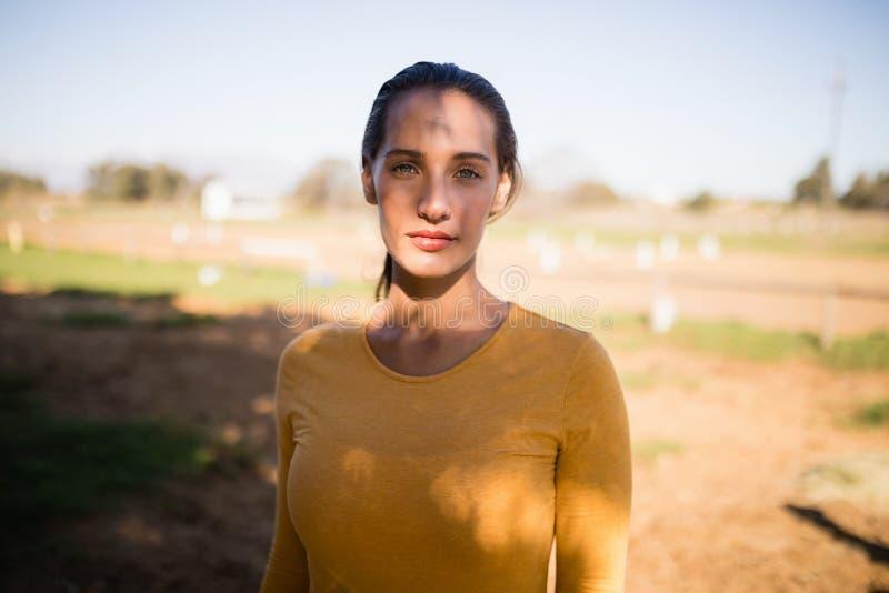 Porträt des ernsten weiblichen Jockeys, der auf Feld steht stockbild