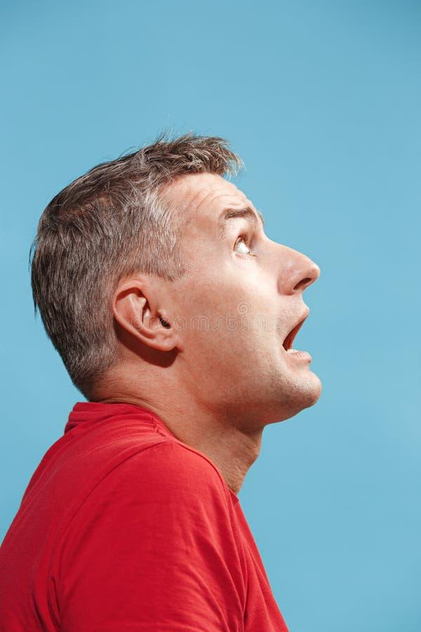 Porträt des erschrockenen Mannes auf Blau stockbild