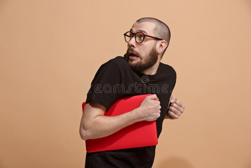 Porträt des erschrockenen Mannes mit Laptop auf Pastell lizenzfreie stockfotos