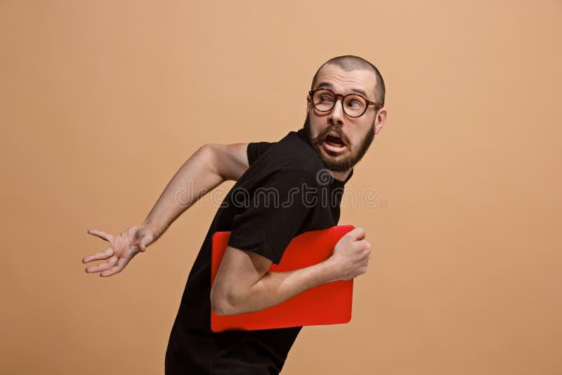 Porträt des erschrockenen Mannes mit Laptop auf Pastell stockfotos