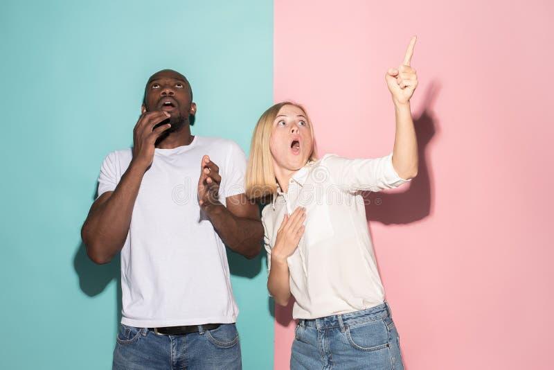 Porträt des erschrockenen Mannes und der Frau auf Rosa und Blau lizenzfreies stockbild