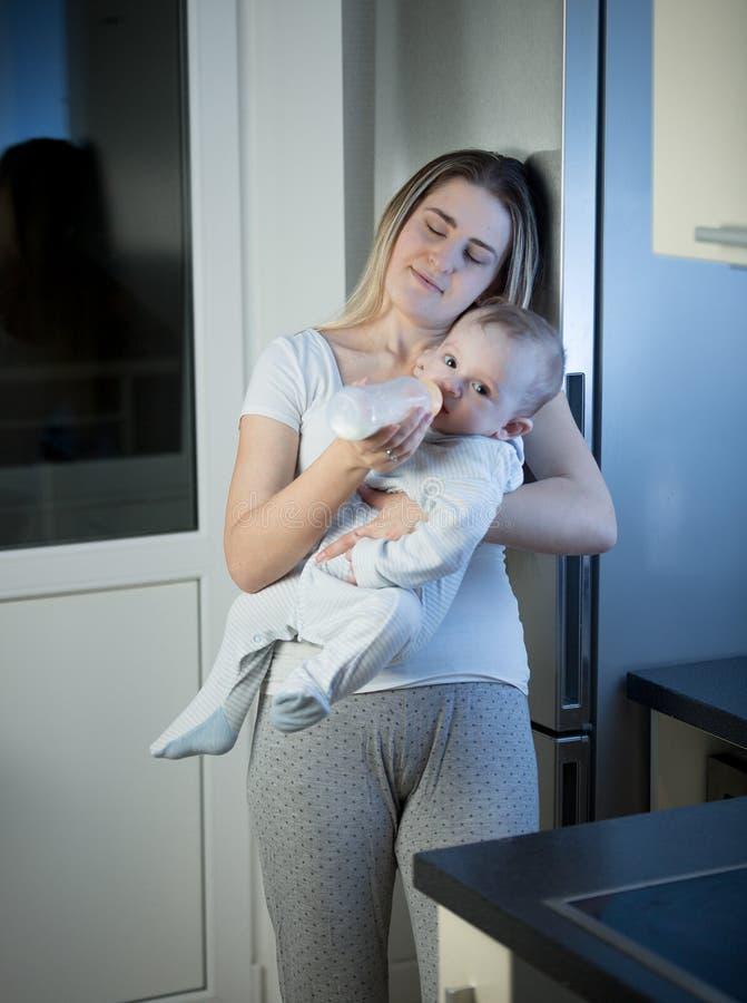 Porträt des Fütterungsbabysohns der schläfrigen Mutter von der Flasche auf kitche stockbilder