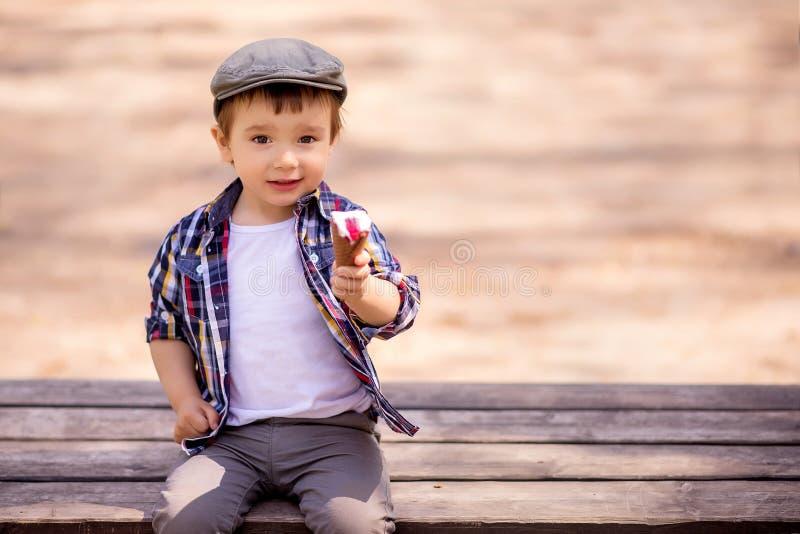 Porträt des fantastischen Kleinkindkindes, das auf der Bank im Freien sitzt und eine Eiscreme anbietet, Nachtisch mit ihm zu teil stockbilder