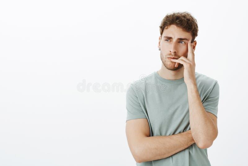 Porträt des fokussierten intelligenten und kreativen männlichen Modells mit dem kurzen gelockten Haar, Finger auf der Lippe und B lizenzfreie stockfotografie