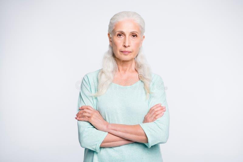 Porträt des fokussierten Rentners mit den gekreuzten Armen, welche die tragende Türkisstrickjacke lokalisiert über weißem Hinterg lizenzfreies stockfoto