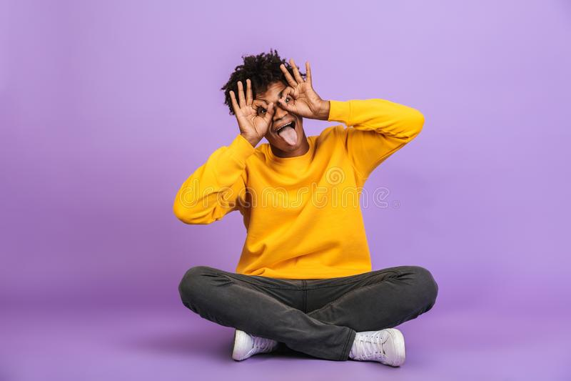 Porträt des frohen Afroamerikanerkerls, der auf Boden mit Le sitzt lizenzfreie stockfotografie