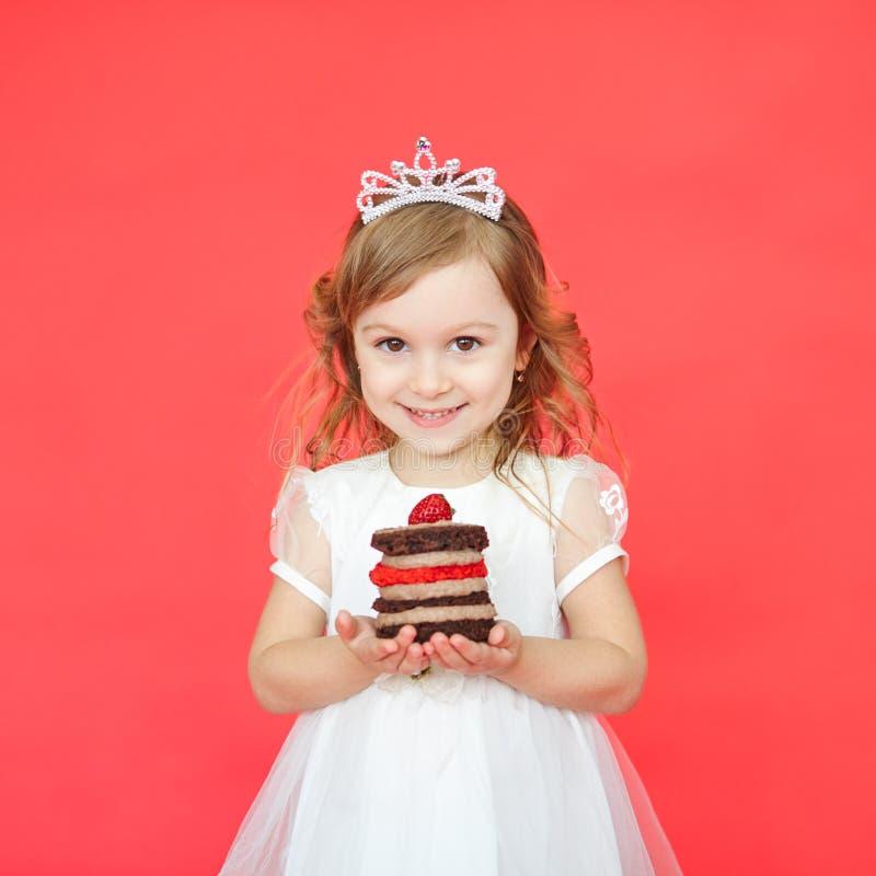 Porträt des frohen kleinen Mädchens mit Kuchen ihren Geburtstag feiernd stockfoto