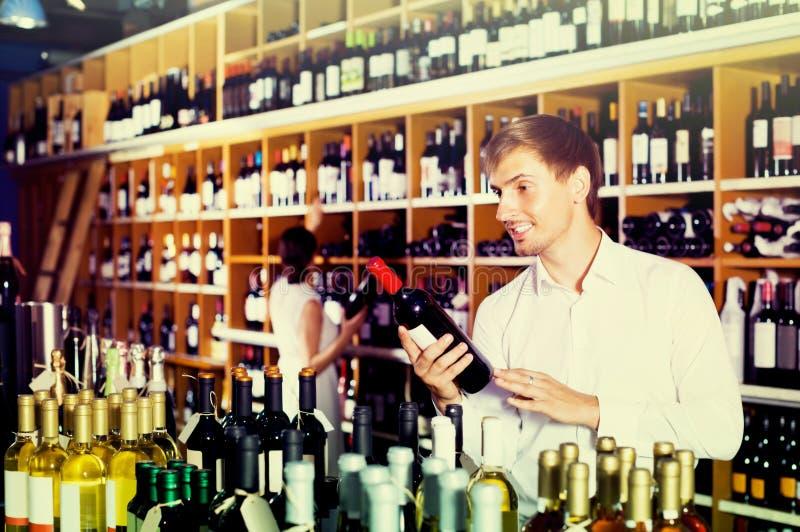 Porträt des frohen männlichen Kunden, der Flasche Wein im Speicher nimmt stockbilder