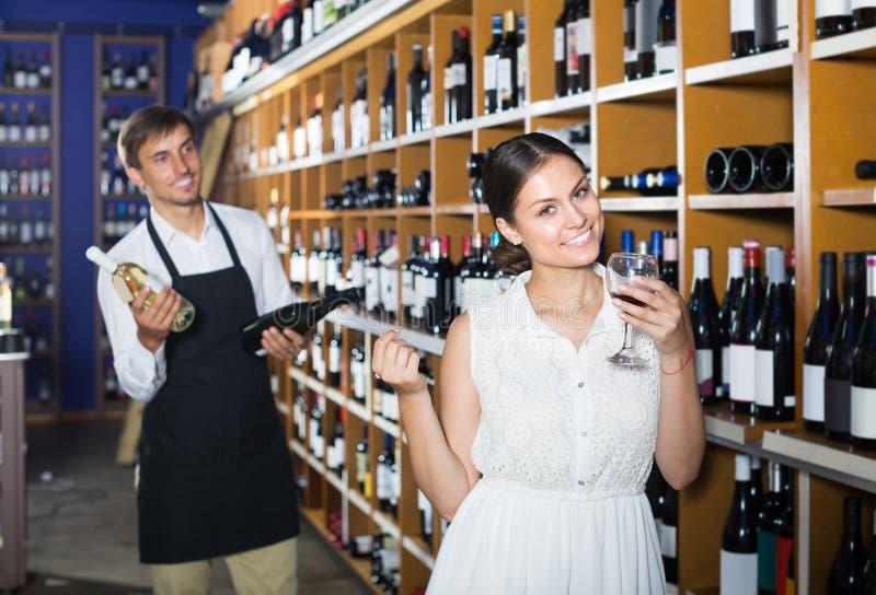 Porträt des frohen weiblichen Kundenprobierenweins vor dem Kauf lizenzfreie stockfotografie