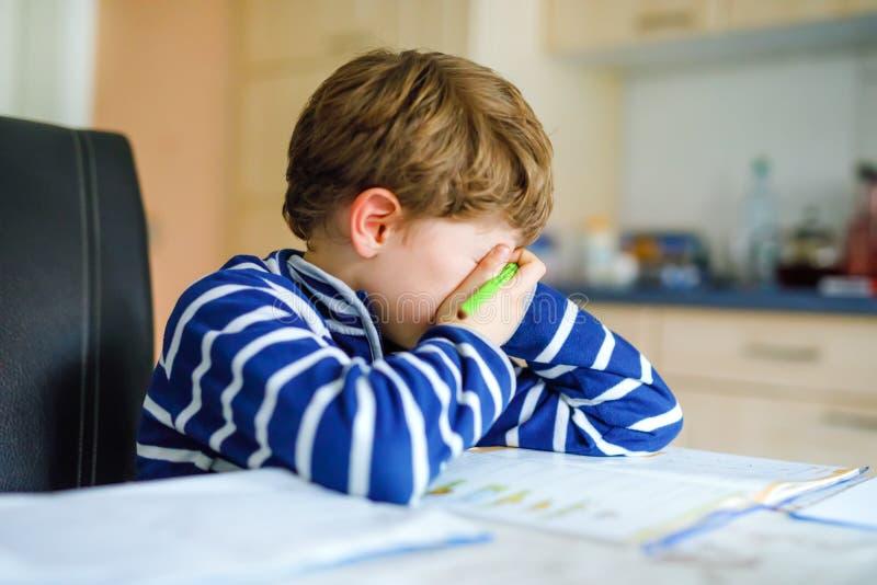 Porträt des frustrierten schreienden traurigen Schulkinderjungen zu Hause, der Hausarbeit macht Kleines Kinderschreiben mit bunte stockfoto