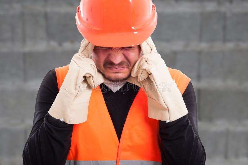Porträt des fustrated Arbeiters mit Kopfschmerzen stockfotografie