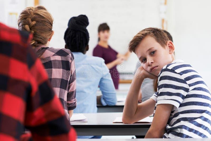 Porträt des gebohrten Jugendschülers in der Klasse stockfotos