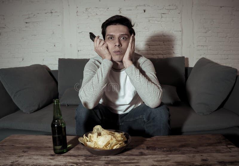 Porträt des gebohrten schlaflosen jungen Mannes, der auf der Couch fernsieht und trinkt Bier nachts sitzt lizenzfreie stockfotos