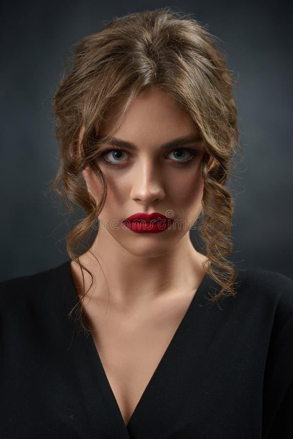Porträt des gelockten Mädchens schwarzes Hemd und roten Lippenstift tragend lizenzfreies stockfoto