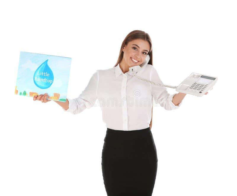 Porträt des Geschäftsfrauholdingbuches für Kinder und der Unterhaltung am Telefon gegen weißen Hintergrund stockbild