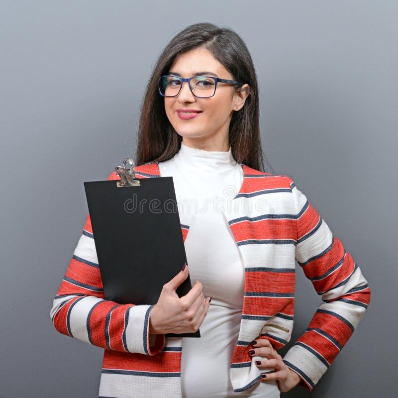 Porträt des Geschäftsfrauholdingklemmbrettes gegen grauen Hintergrund lizenzfreies stockbild