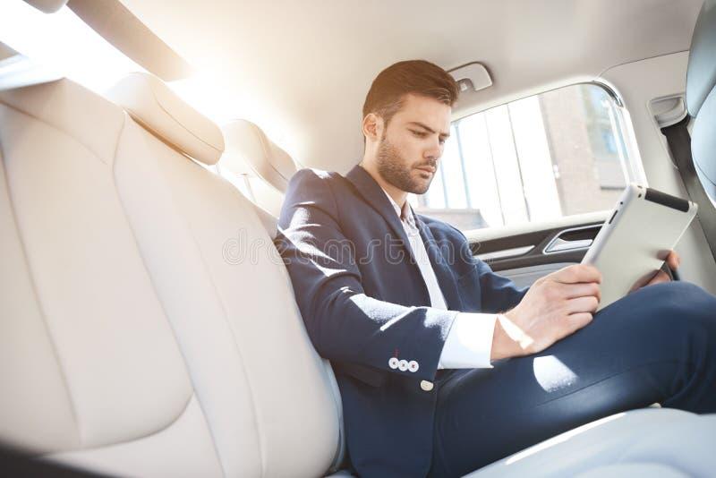 Porträt des Geschäftsmannes, der digitale Tablette beim Reisen verwendet lizenzfreies stockfoto