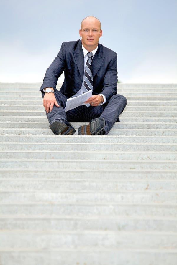 Porträt des Geschäftsmannes Dokument auf Schritten verwahrend stockbilder