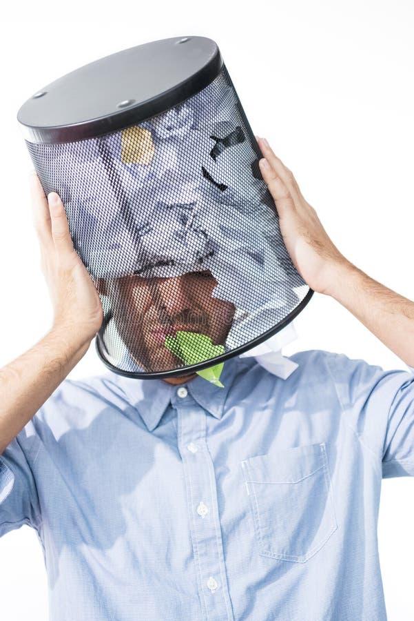 Porträt des Geschäftsmannes mit Abfalleimer auf Kopf im Büro lizenzfreies stockfoto
