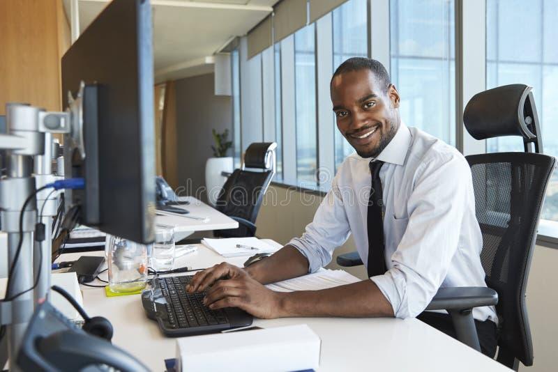 Porträt des Geschäftsmannes At Office Desk, das Computer verwendet lizenzfreies stockbild