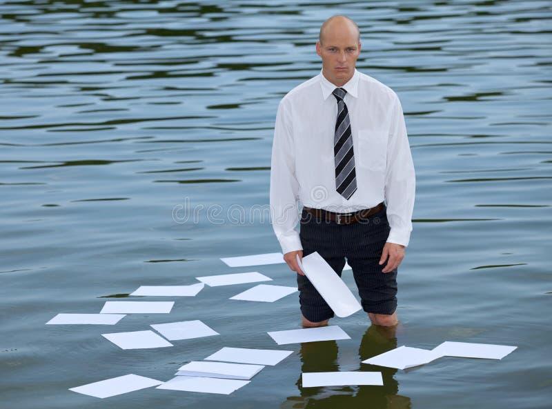 Porträt des Geschäftsmannes stehend im See mit den Papieren, die auf Wasser schwimmen lizenzfreies stockbild