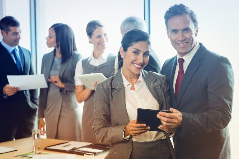 Porträt des Geschäftsmannes und Geschäftsfrau, die digitale Tablette hält lizenzfreie stockbilder