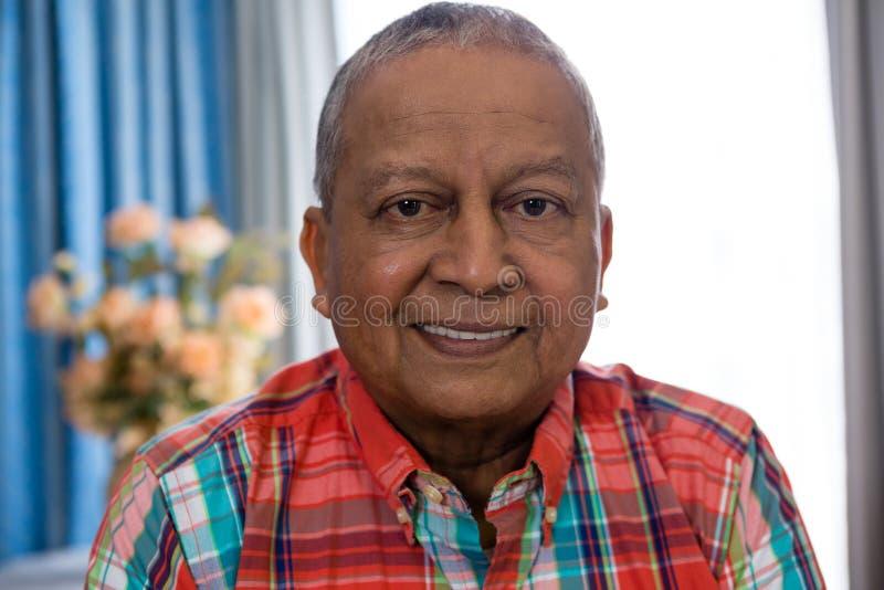 Porträt des glücklichen älteren Mannes, der im Pflegeheim sich entspannt stockfoto