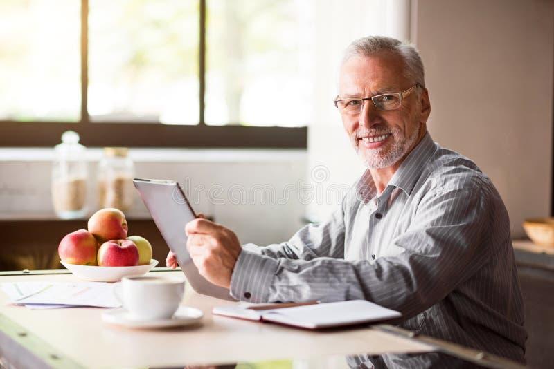 Porträt des glücklichen älteren Mannes, der zu Hause Laptop in der Küche verwendet lizenzfreie stockfotos